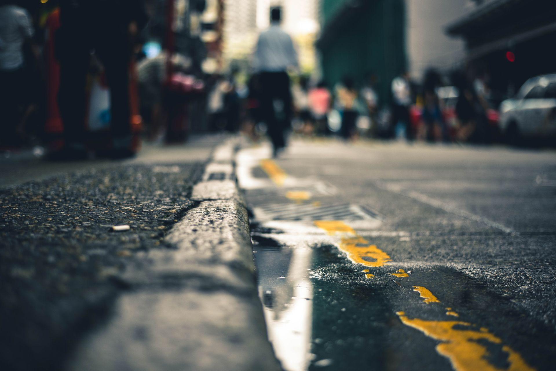 Maatasalta otettu kuva sateenjälkeisestä kadusta, jolla ihmiset kävelevät pois päin kamerasta.