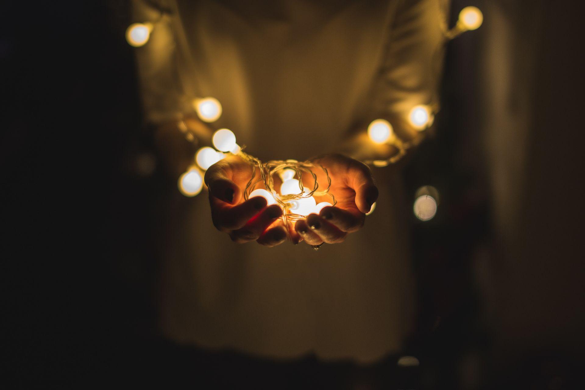 Vaaleaan villapaitaan pukeutunut henkilö pitää käsissään led-valonauhaa.