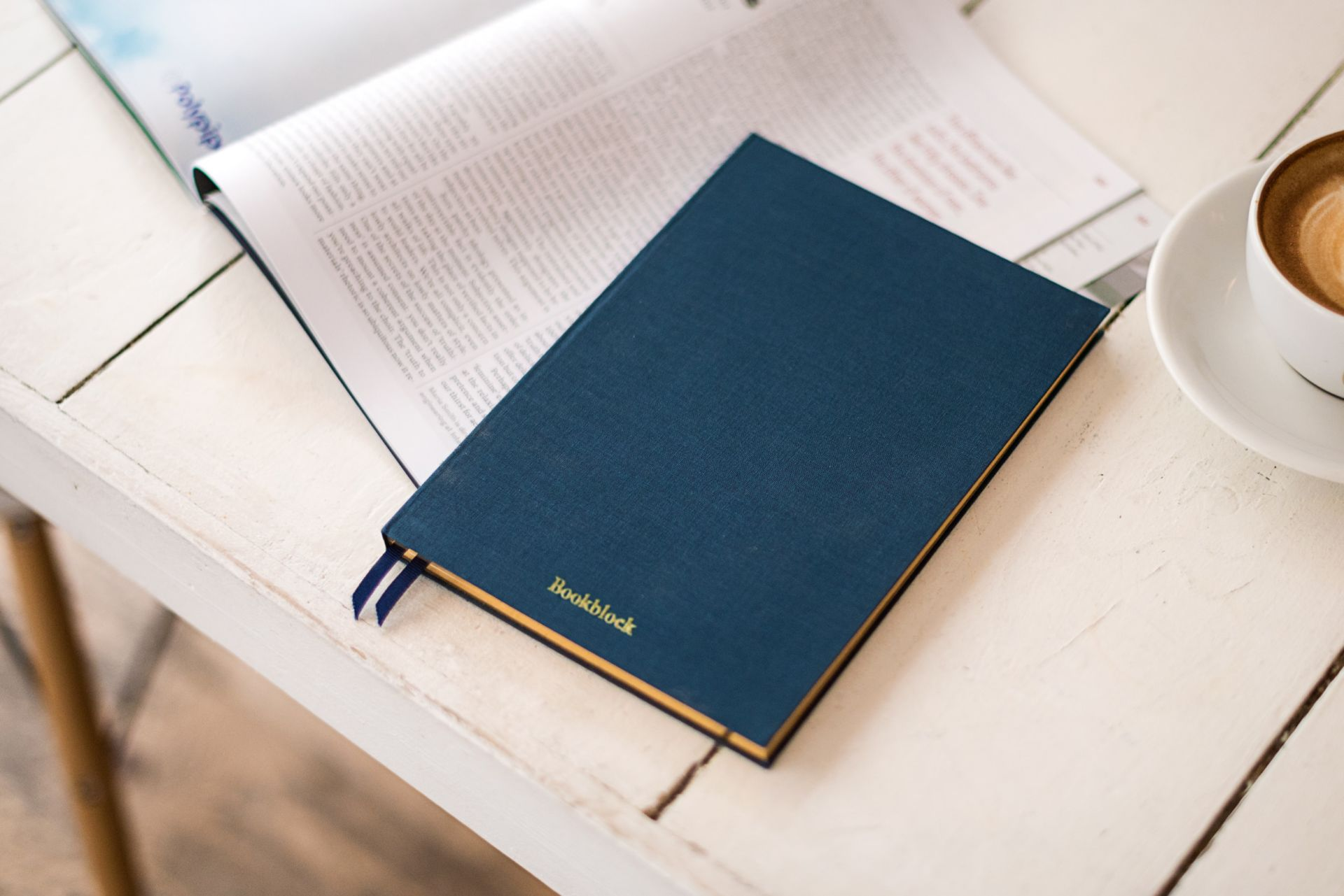 Sininen muistikirja, aikakausilehti ja kahvikuppi pöydällä.