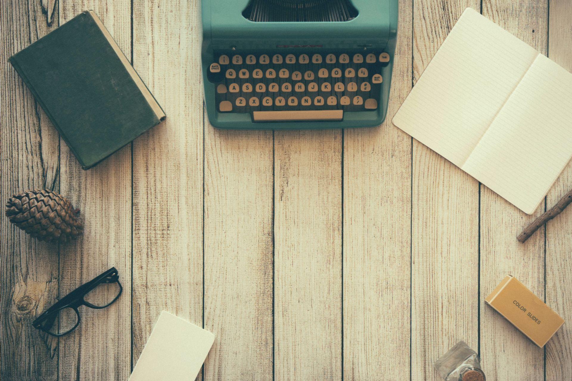 Lautalattialle ympyrään aseteltu kirjoituskone, vihko, puunoksa, pyyhekumi, lasipullo, muistilappu, silmlasit, käpy ja muistikirja.