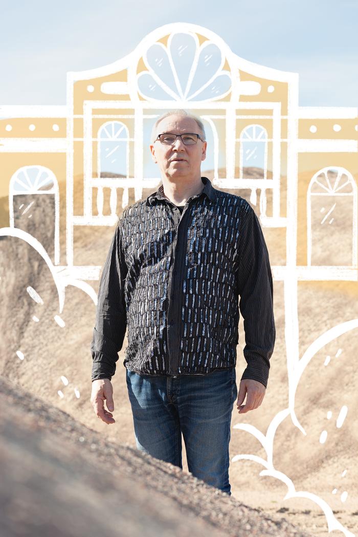 Kuvassa Ennakkoluuloton näyttelyä varten kuvattu mies. Mies seisoo hiekkadyyniin edessä. Kuvan päälle on piirretty huvila.