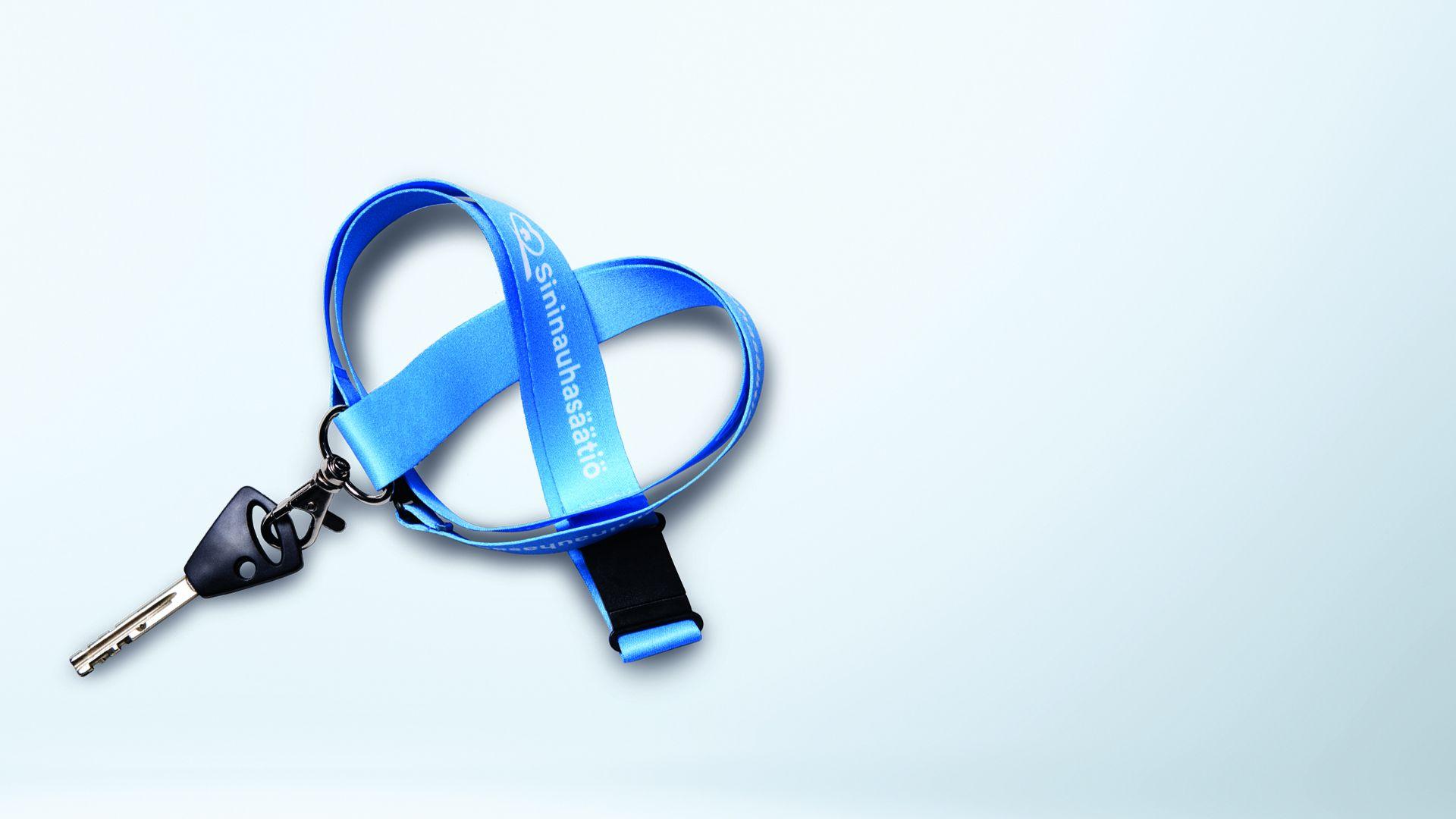 Sydämen muotoon taiteltu sininen avainnauha, jossa lukee Sininauhasäätiö.