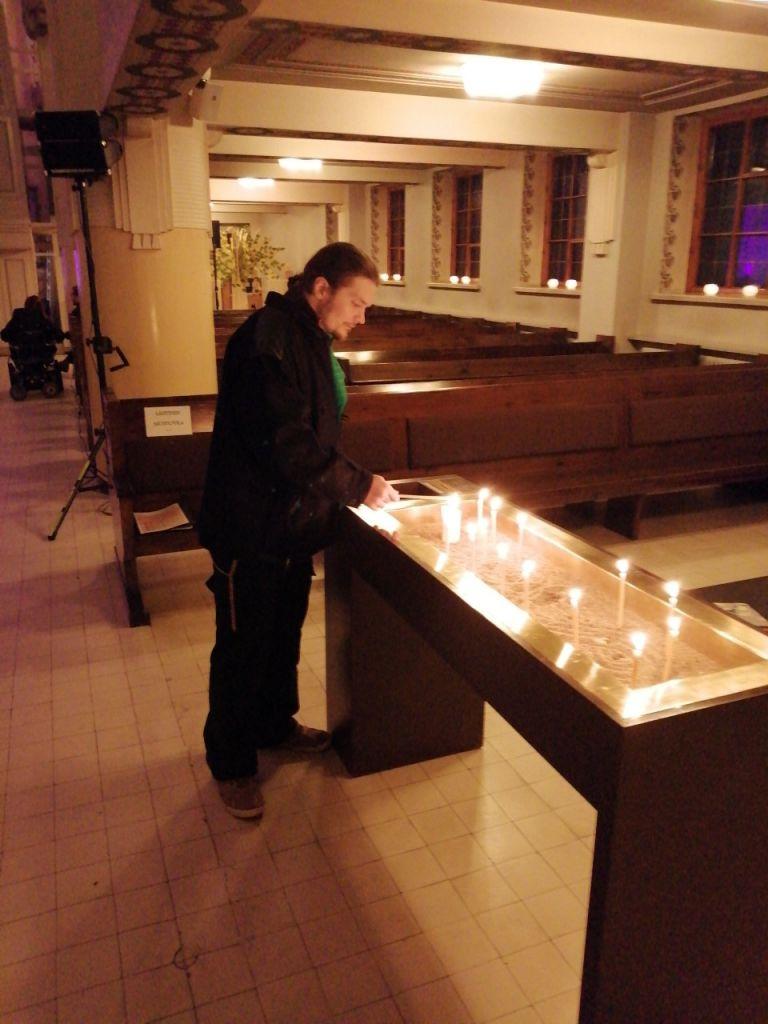Mies sytyttää kynttilän kirkossa.