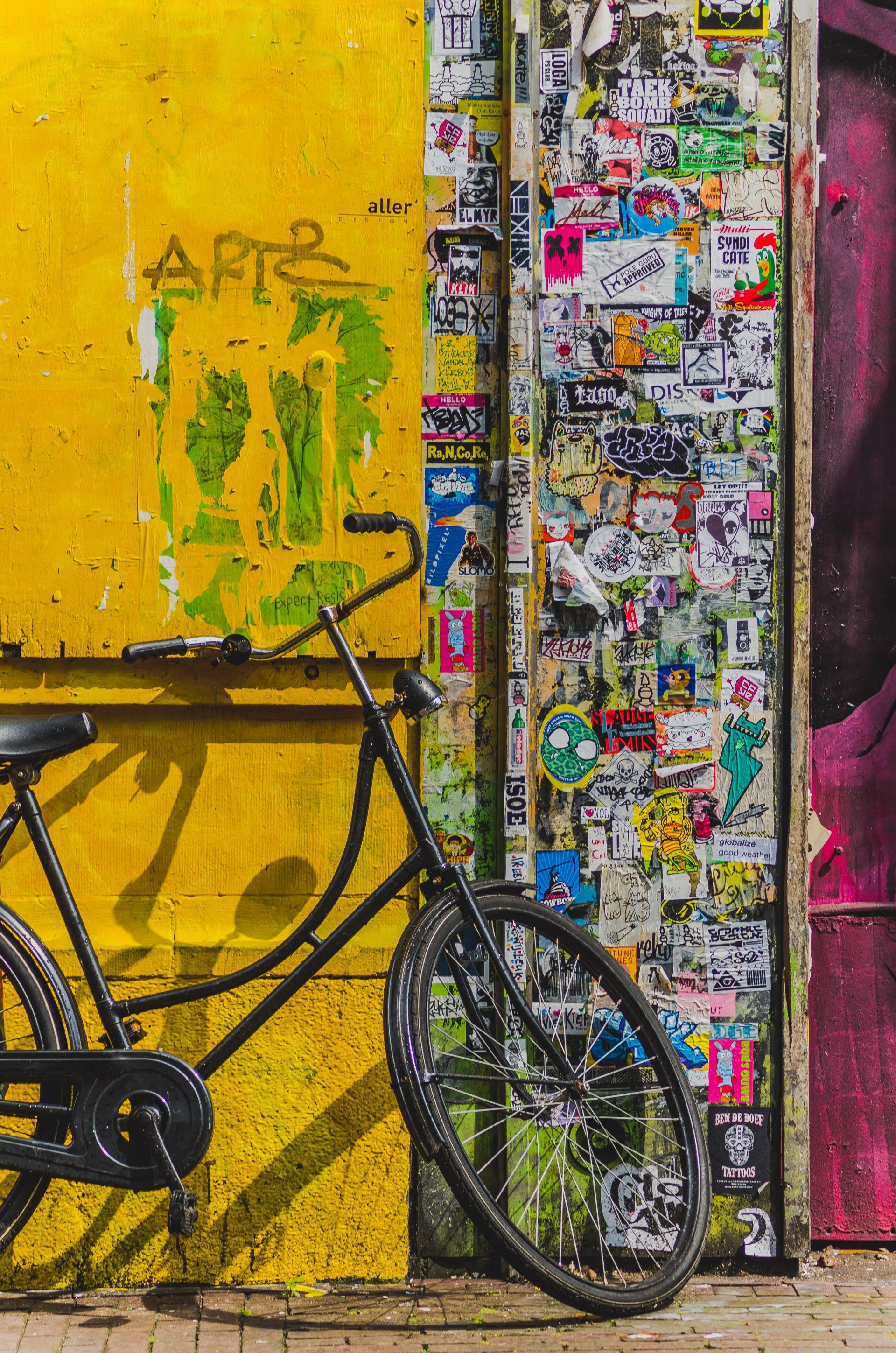 Musta polkupuora nojaa kirkkaan keltaisen rakennuksen seinää vasten. Rakennukset kulma on liimattu täyteen tarroja.