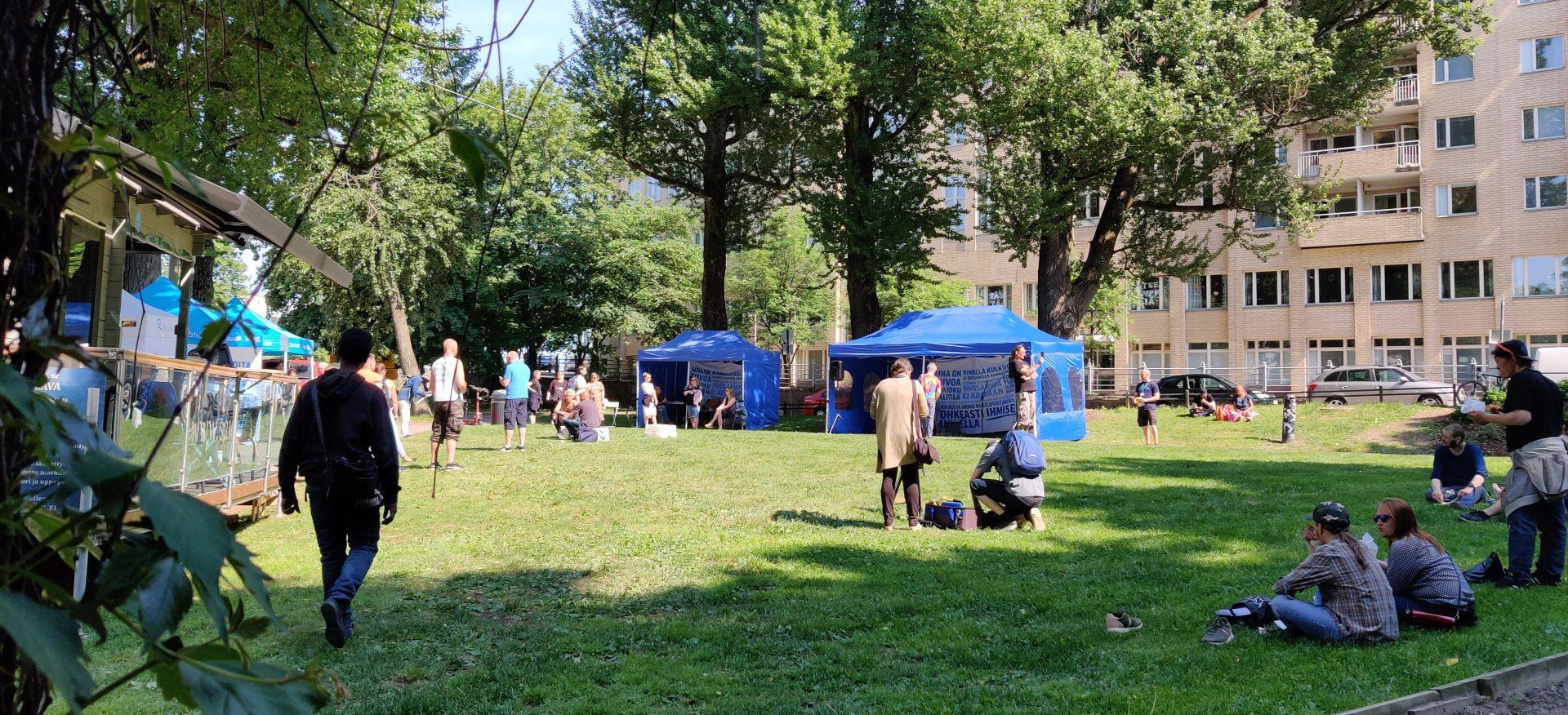 Aurinkoinen puisto, jonka reunoilla on messutelttoja ja nurmikentällä istuu ihmisiä.