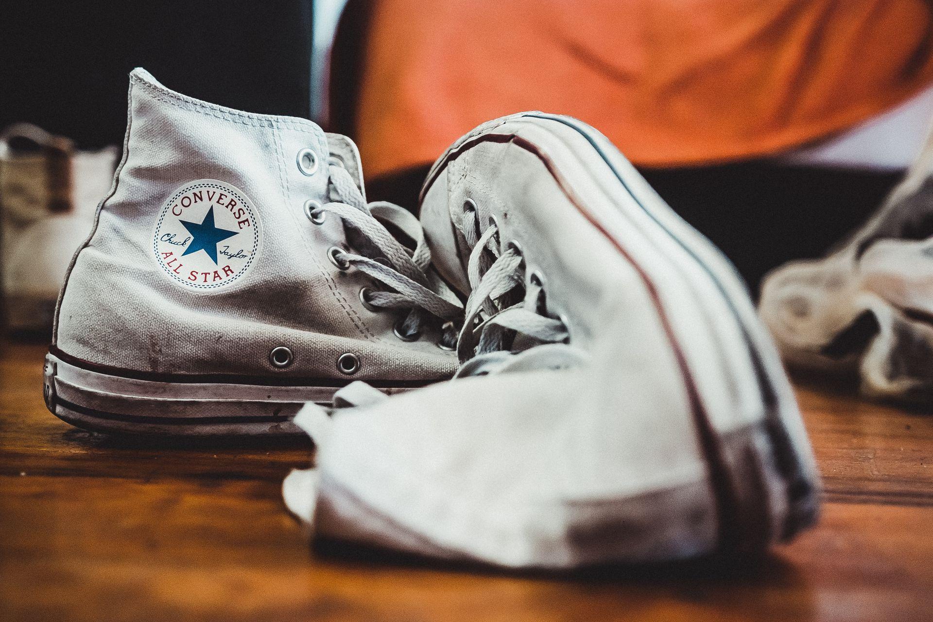 Valkoiset Converse -tennistossut lattialla.