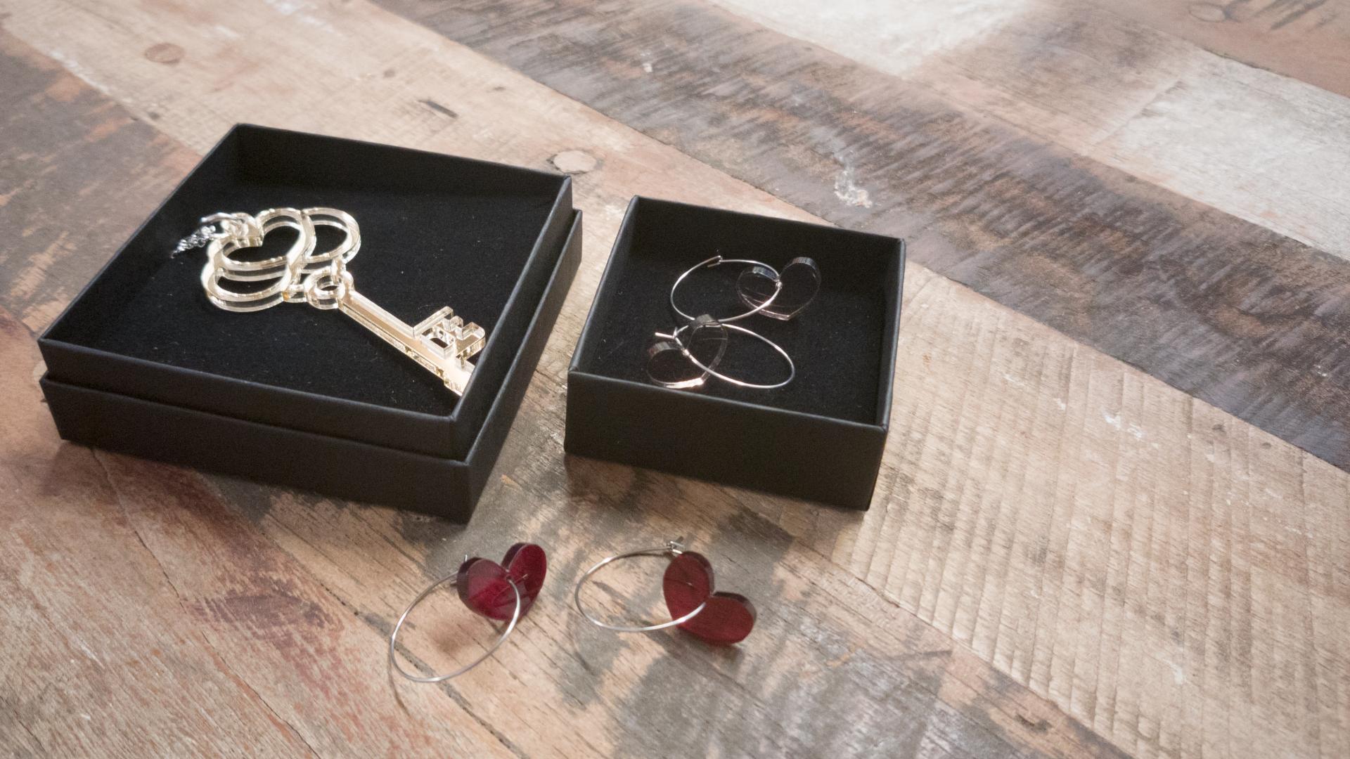 Puisella pöydällä kaksi mustaa korurasiaa, joissa on kultainen avainkaulakoru ja toisessa läpinäkyvät sydämenmuotoiset korvakorut. Niiden edessä pöydällä on toinen pari sydämenmuotoisia punaisia korvakoruja.