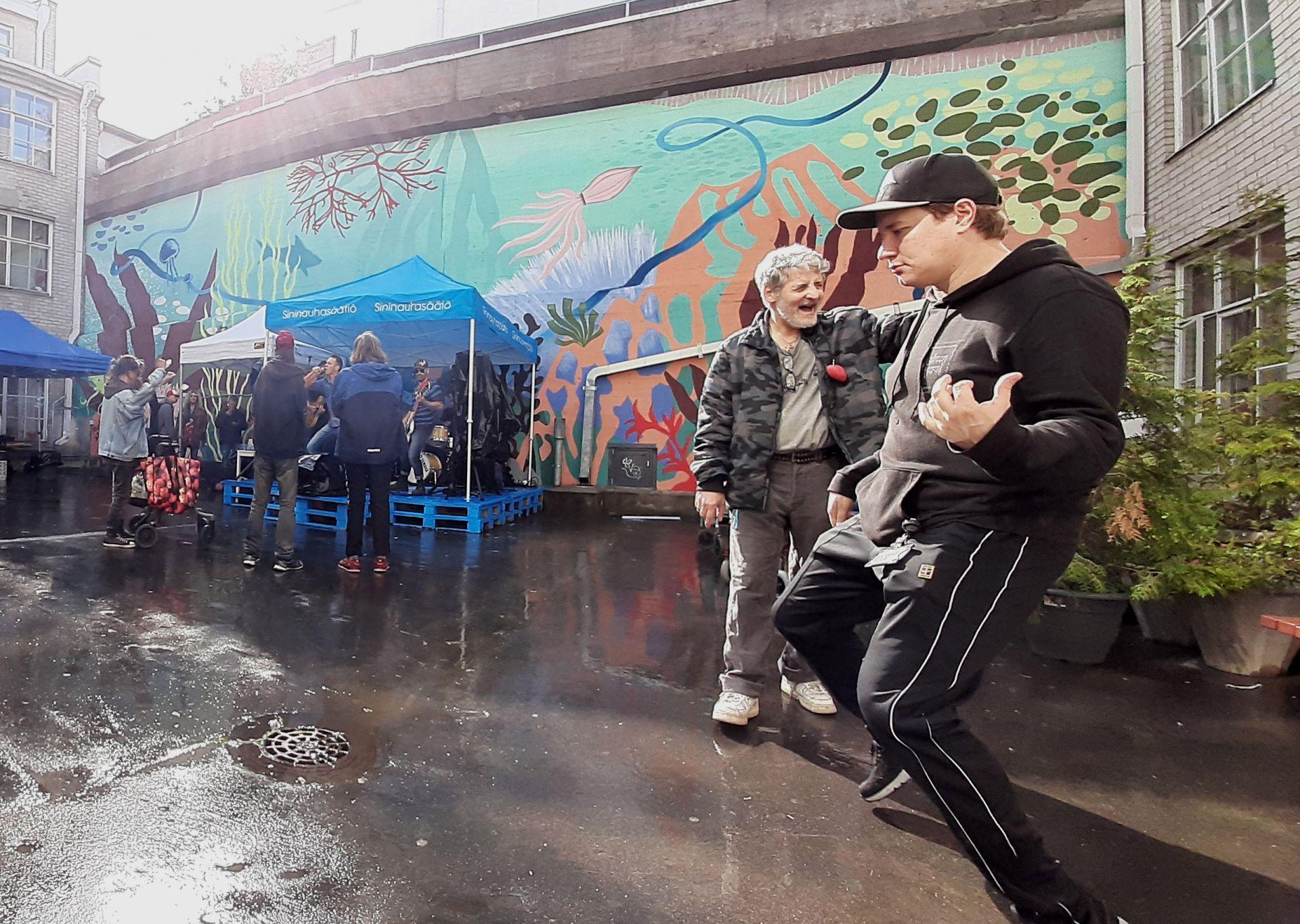 Mies soittaa ilmakitaraa Mäkelänkatu 50 sisäpihalla ja taustalla bändi soittaa pienelle yleisölle sinisten eurolavojen päällä.