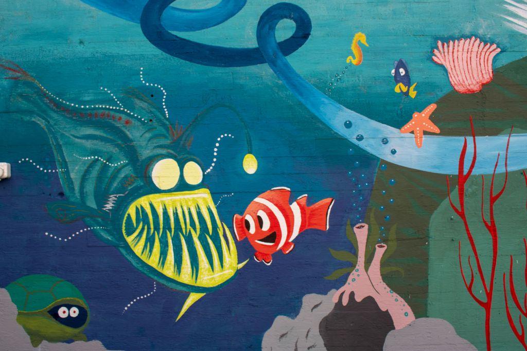 Lähikuvamuraalista. Kuvassa maalattu lyhtykrotti, jonka edessä ui klovnikala.