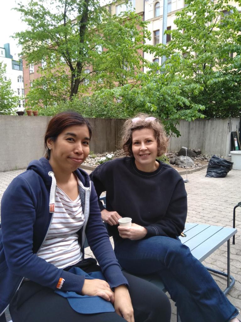 Kaksi naista puiston penkillä betonisella pihalla.