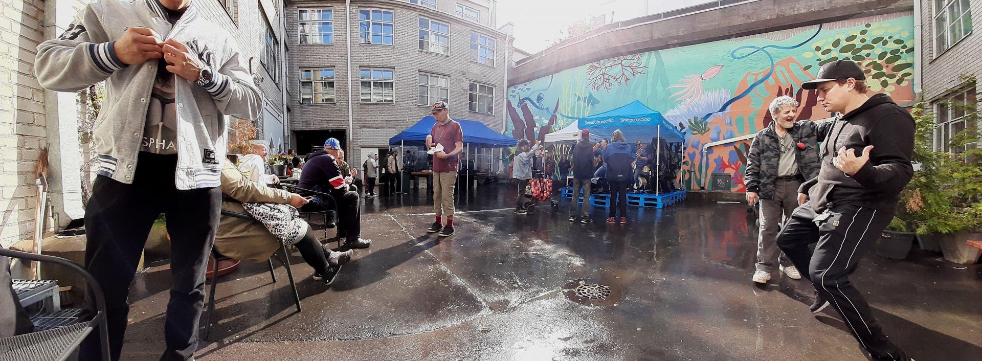Panoramakuva Mäkelänkatu 50 sisäpihasta, jossa ihmiset ruokailevat bändin soittaessa.