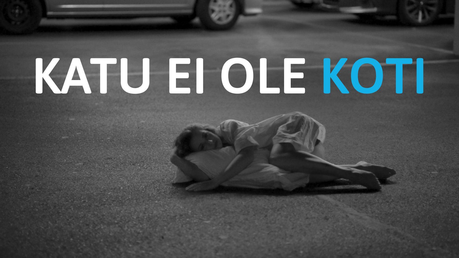 Harmaasävyisessä kuvassa nuori nainen makaa pysäköintitalon lattialla halaten tyynyä.