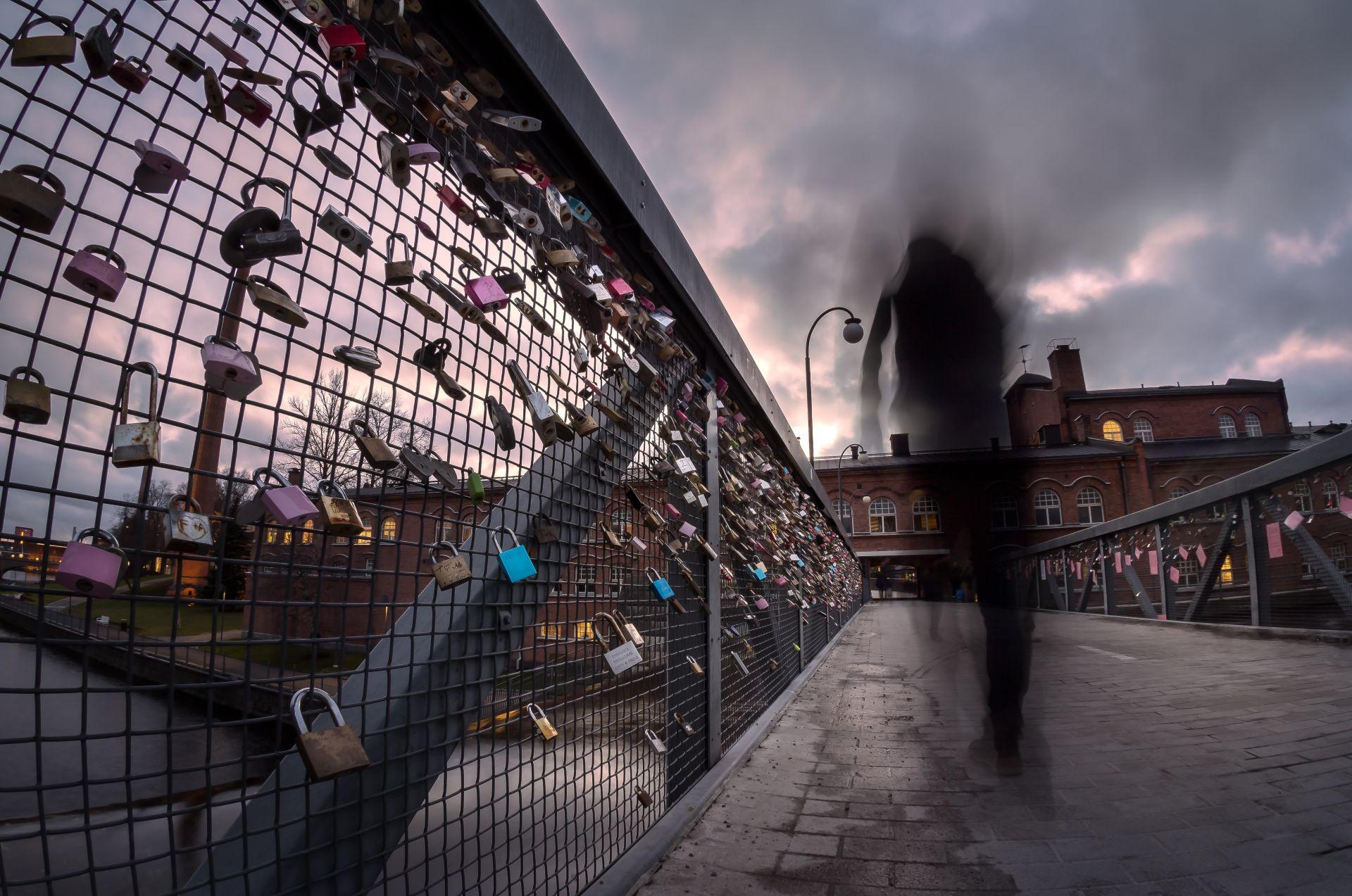 Hahmo sillalla, jossa on lukkoja.