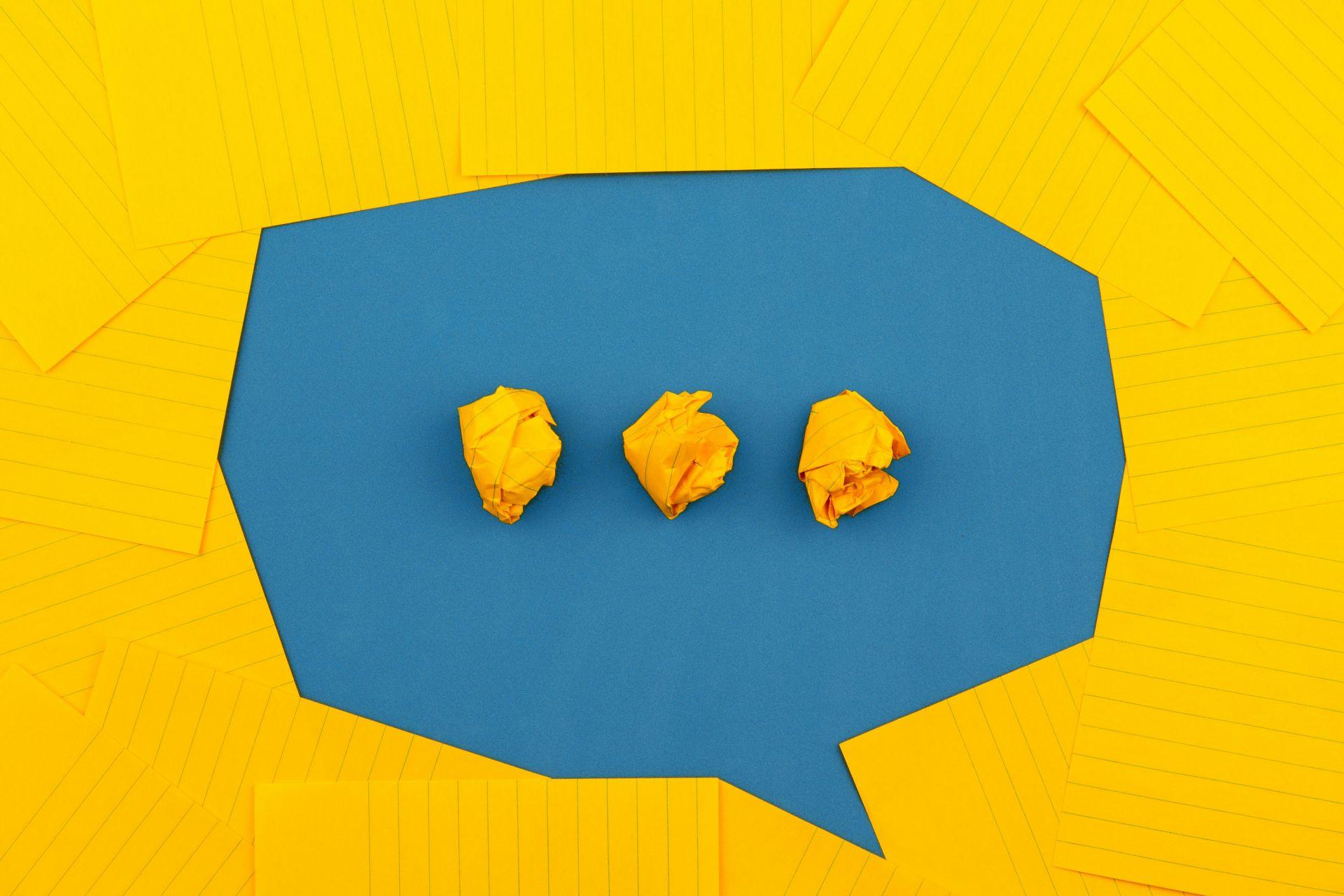 Keltaisista papereista sinistä taustaa vasten muodostettu puhekupla, jossa kolme rypistetystä paperista tehtyä pistettä.