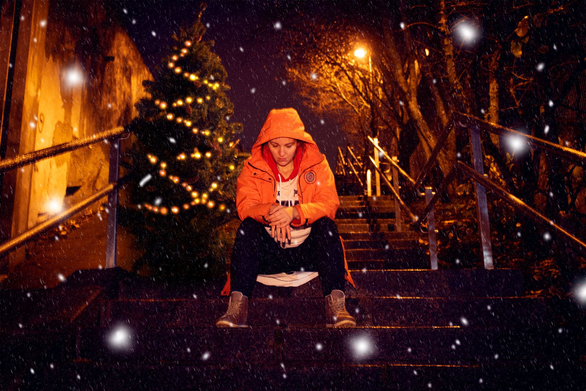 Nuori istuu betoniportailla lumisateessa, taustalla näkyy joulukuusi.