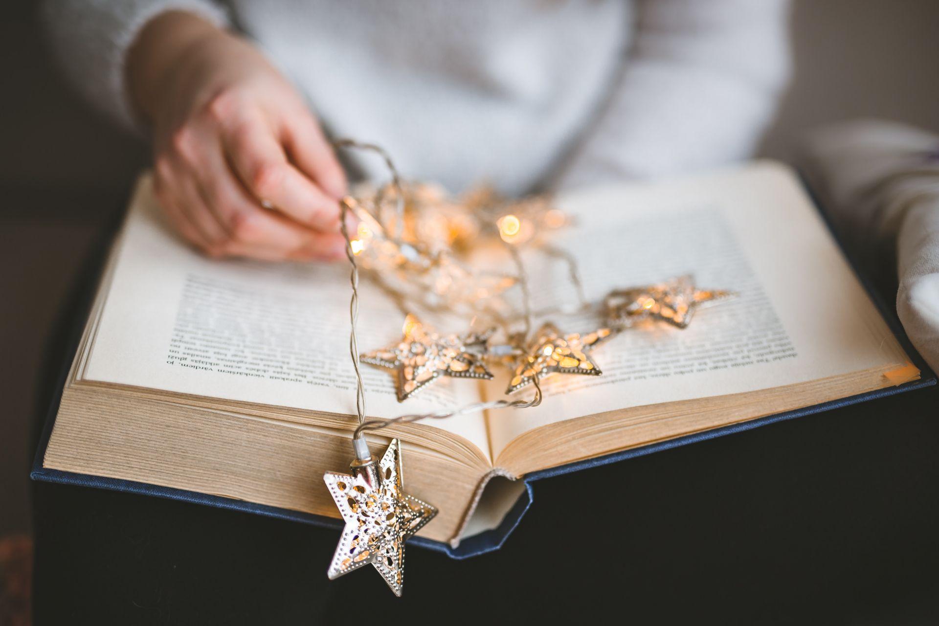 Kirjaa pitelevät kädet ja tähtivalonauha.