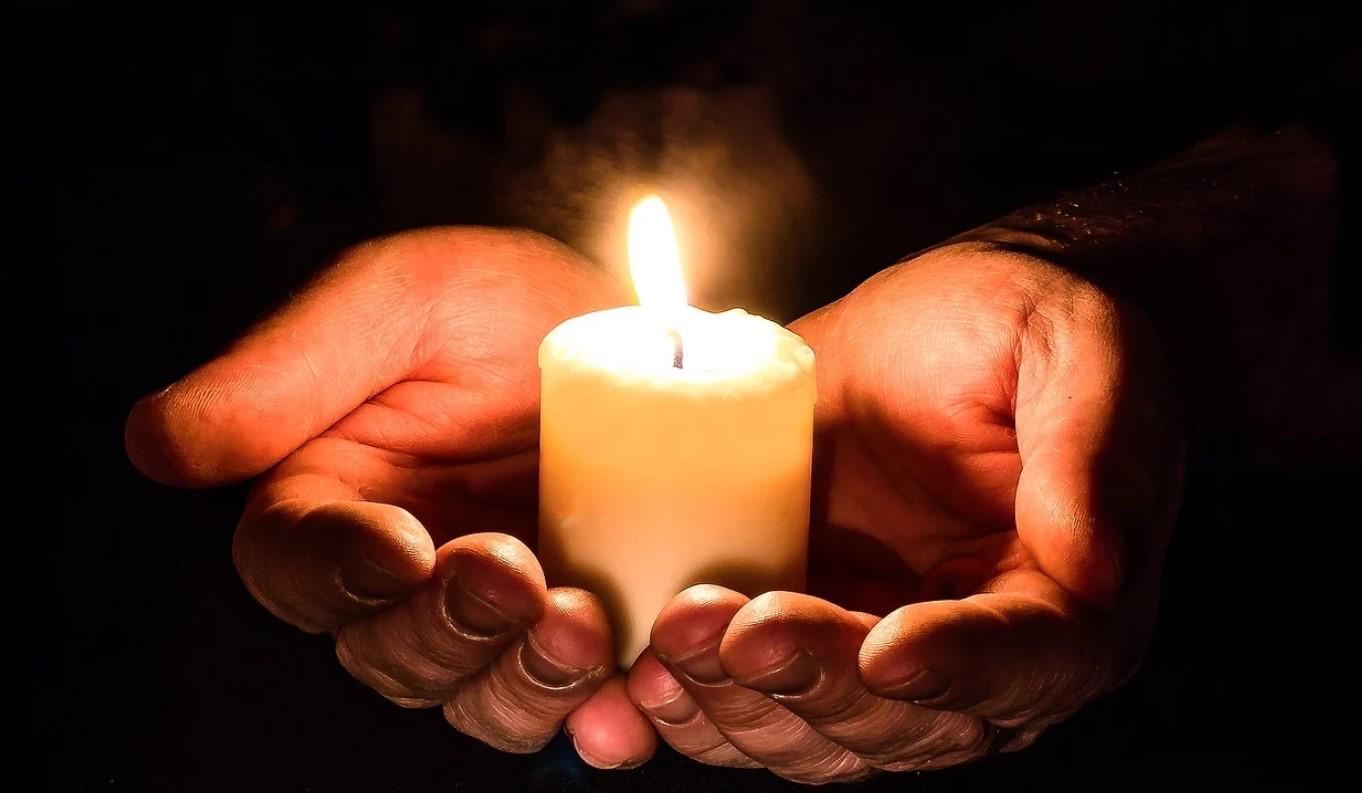 Kynttilä käsissä.