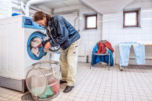 Mies lastaa pyykkiä pyykinpesukoneeseen.