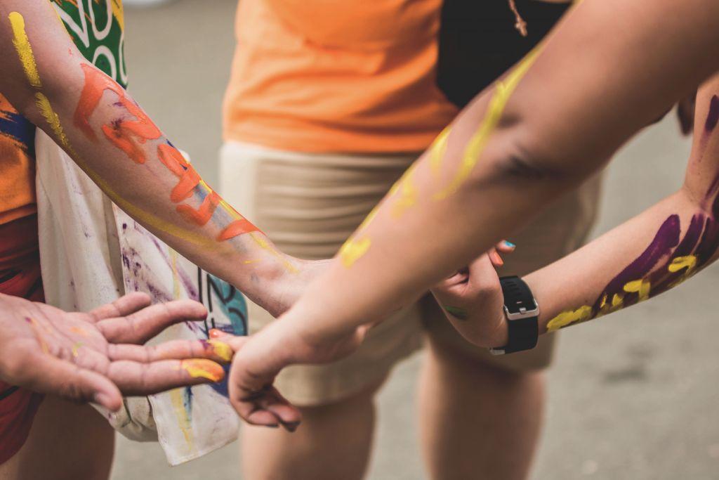 Käsiä, joissa maalitahroja
