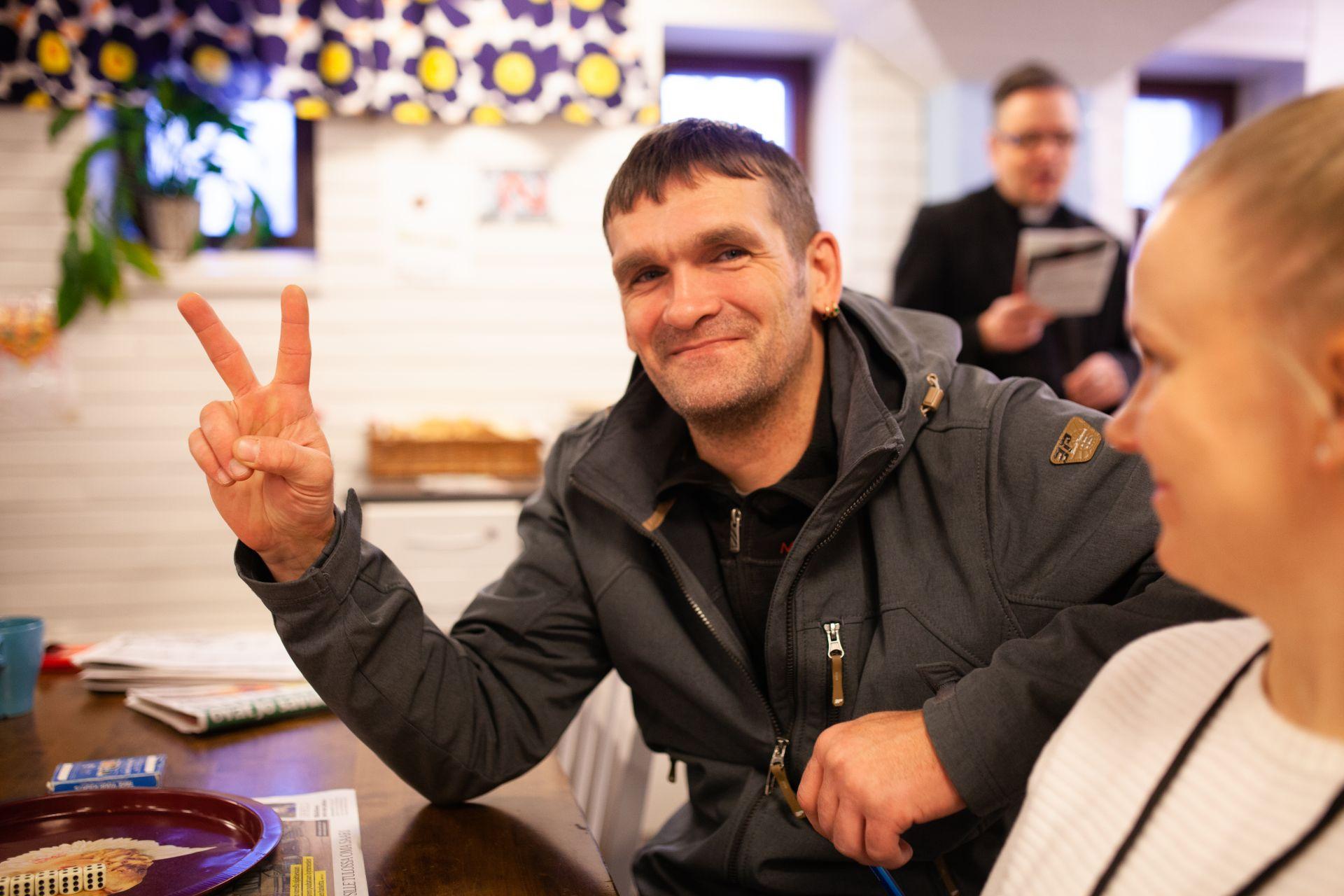 Hymyilevä mies näyttää rauhanmerkkiä