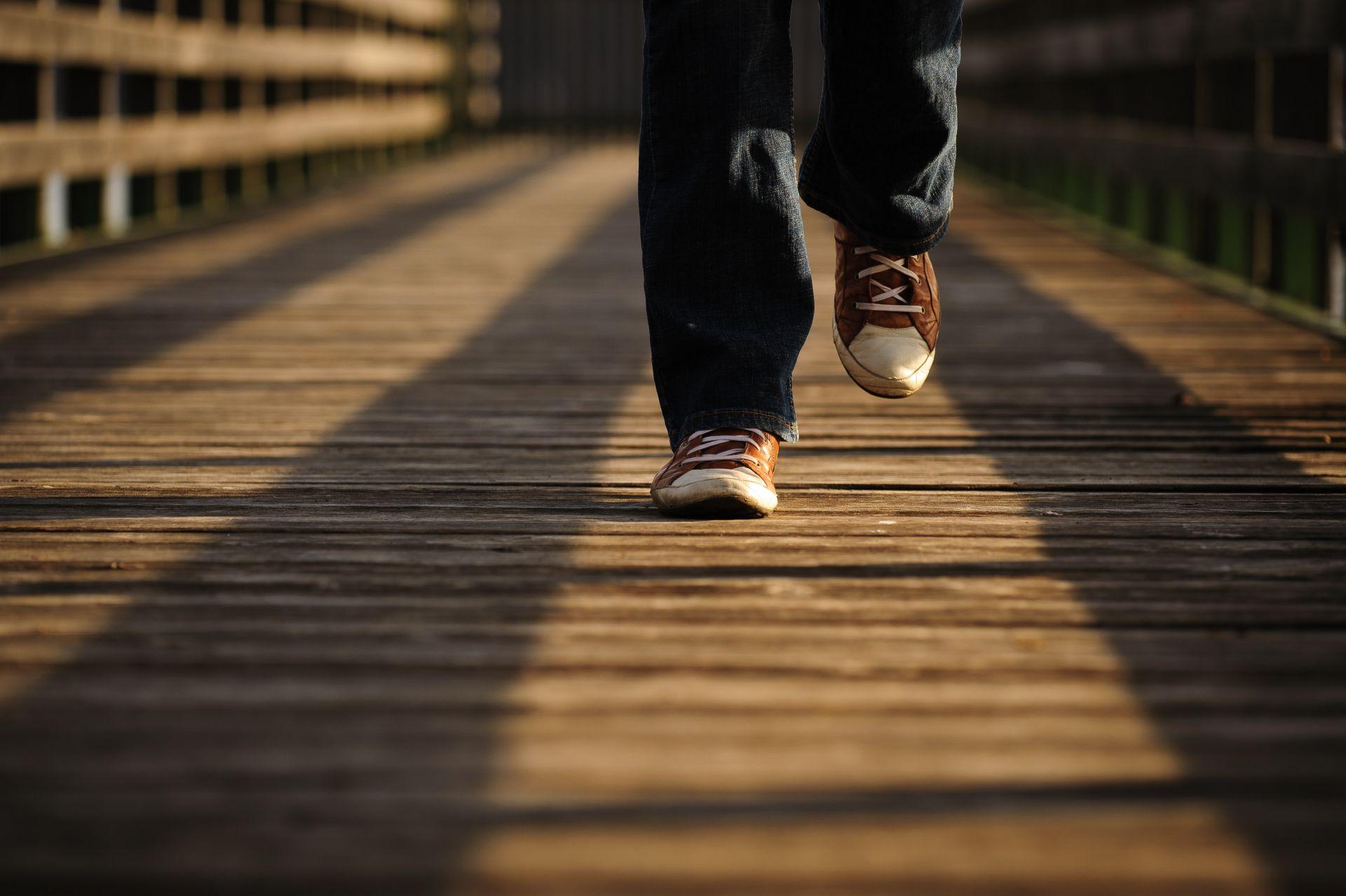 Kuvituskuva, henkilö kävelee puisella sillalla