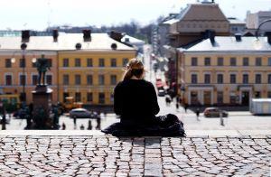 Nainen istuu Tuomiokirkon portailla Helsingissä.