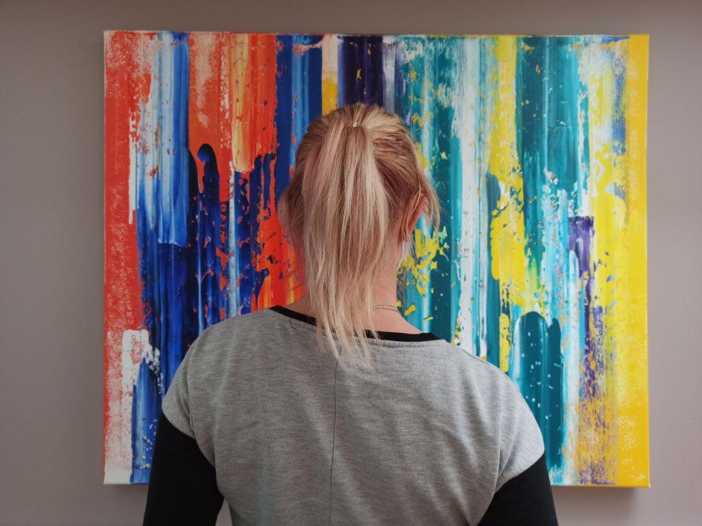Kuva naisesta maalauksen edessä