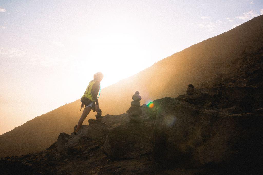 Henkilö kiipeää vuoren rinnettä, valokuva.
