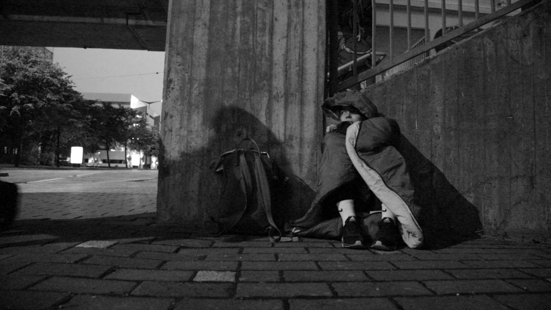 Mustavlkoinen kuva makuupussiin kietoutuneesta nuoresta kadulla, joka pelästyy ohikulkijoiden varjoja.