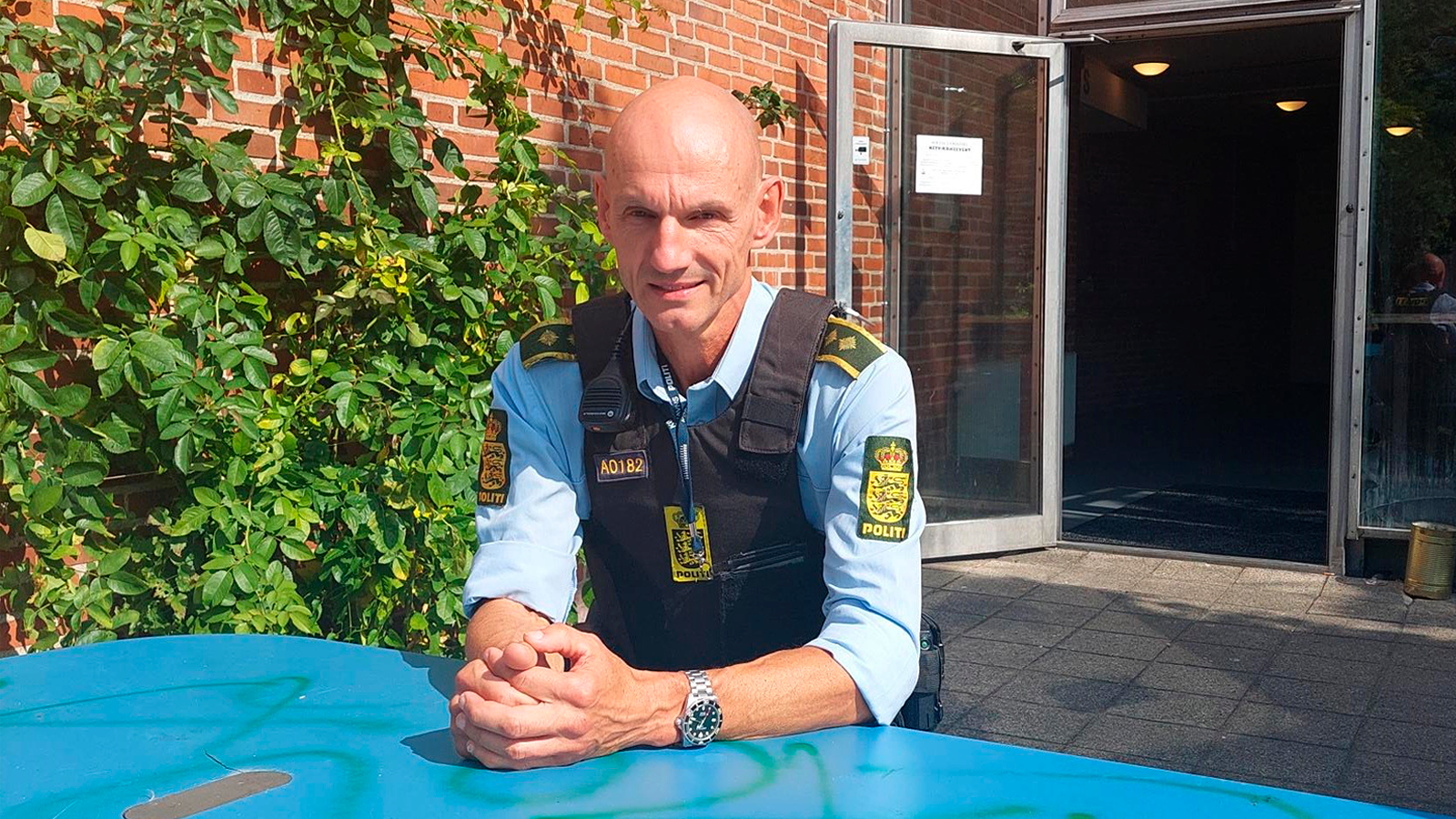 Iäkäs miespuolinen poliisi asuinyksikön edessä