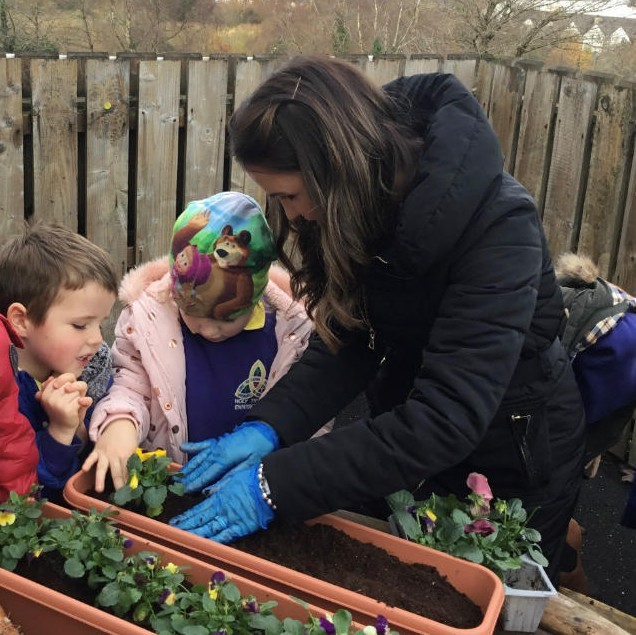 Enjoying planting with Mrs Colhoun in P1