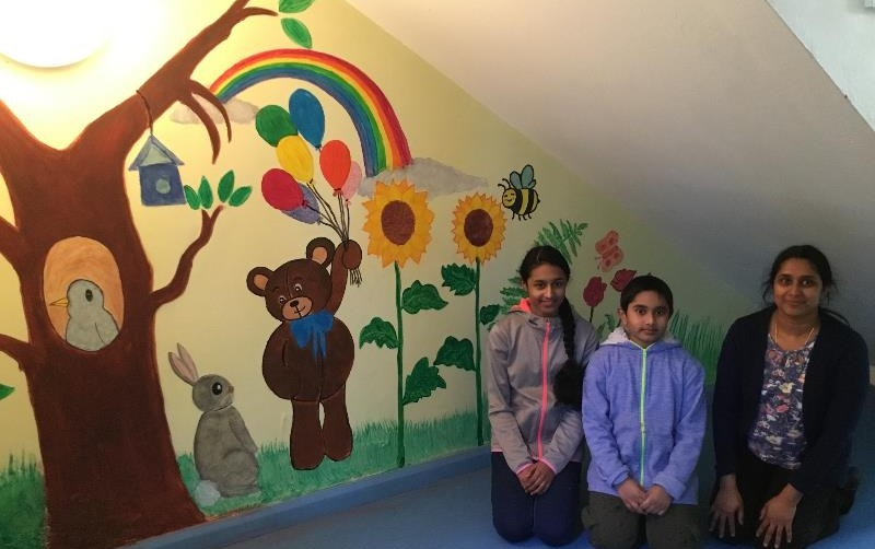 Liji, Anjali and Arjun beside the beautiful mural they which they painted in P1