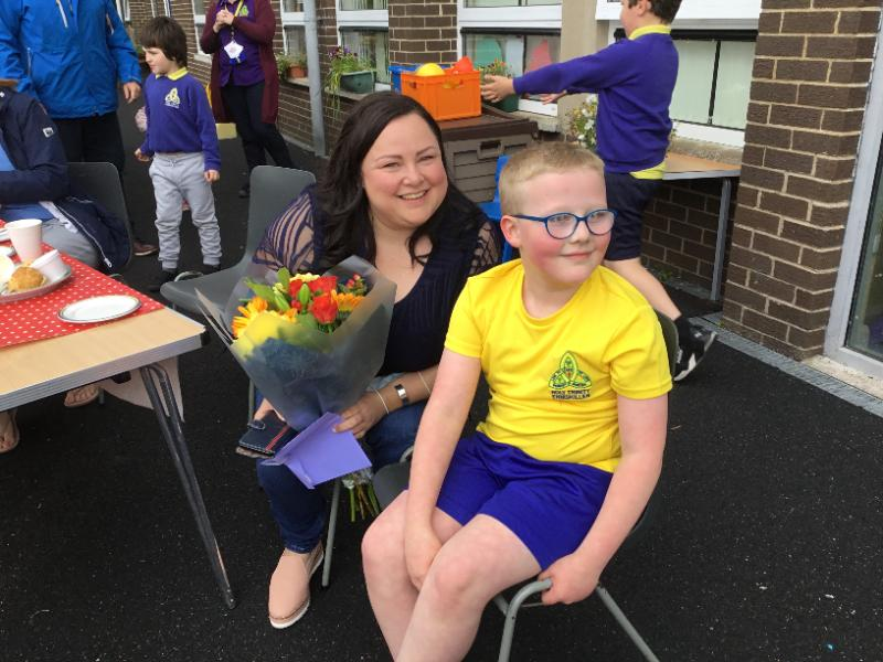 Jack presents his mum with flowers and a thank  you card from Miss Corrigan;s AS class.  Thank you to Debbie who has raised alot of money for a new sensory room.