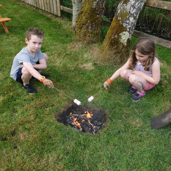 Toasting marshmallows in a pit in the garden, Yum!