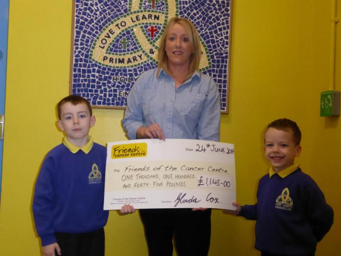 Oisin, Glenda and Eoin hold a cheque for £1145, Glenda raised this money for the charity 'Friends of the Cancer Centre'