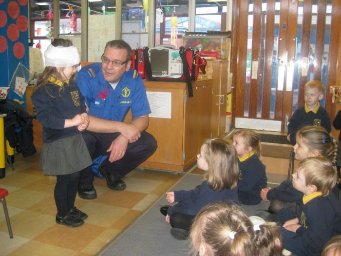Alex showing the other children the bandage on her head