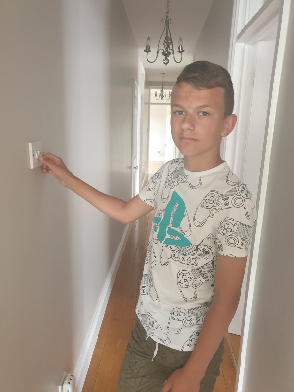 Kacper switching off lights at home to save energy