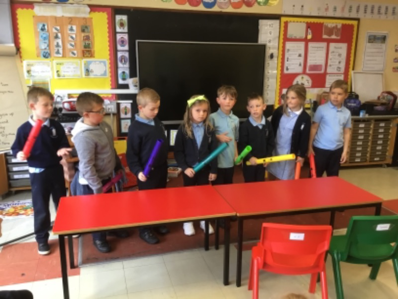 Striking boomwhackers to hear the scale.