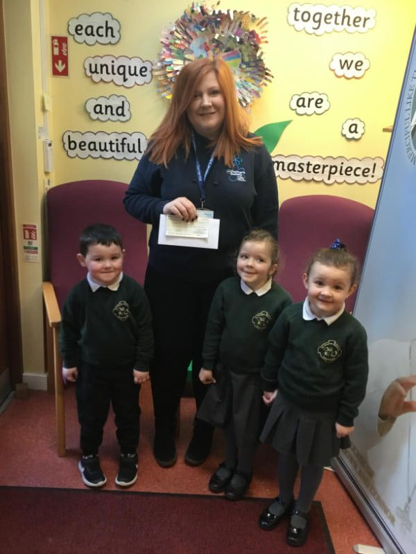 Saul, Ellen and Eimear present a cheque to Suzanne from the Alzheimers Society