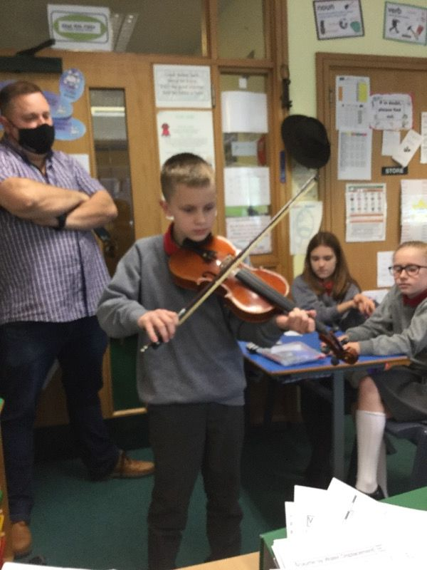Alfie demonstrates his fiddle playing talent.