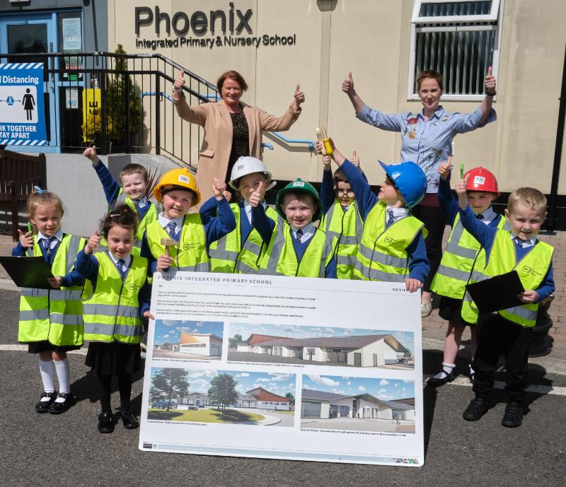 Pupils from Phoenix Integrated Nursery and Primary School along with Mrs. Heather Watson (Principal) and Mrs. Liz Simpson (Chair of Board of Governors) examine the plans for a new school building on the current site.