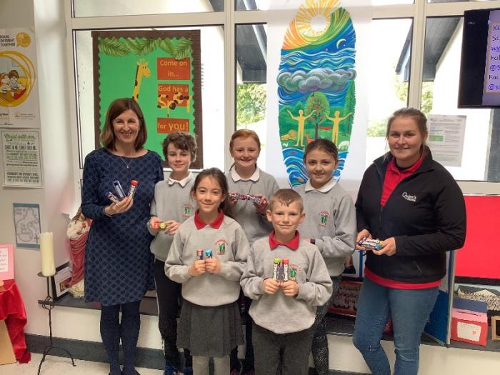 Mrs Sealey with Aaron, Ava, Sophia, Aoibhlínn and Joshua getting their Smarties from Kirsty! Thanks to the Spar!