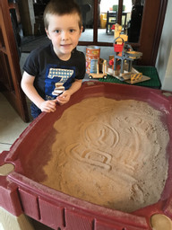 James practising his weekly letter in the sand.