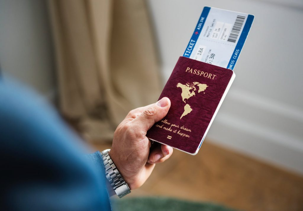 male hand holding passport and airline tickets