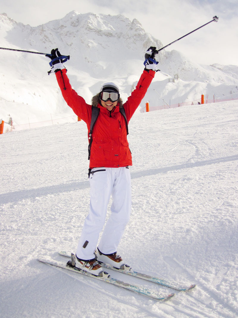 Adult beginner skier celebrates with arms in air