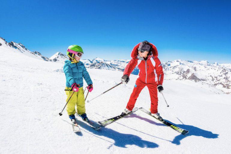 private ski instructor in red ski suit gives tips to child in kids private ski lesson