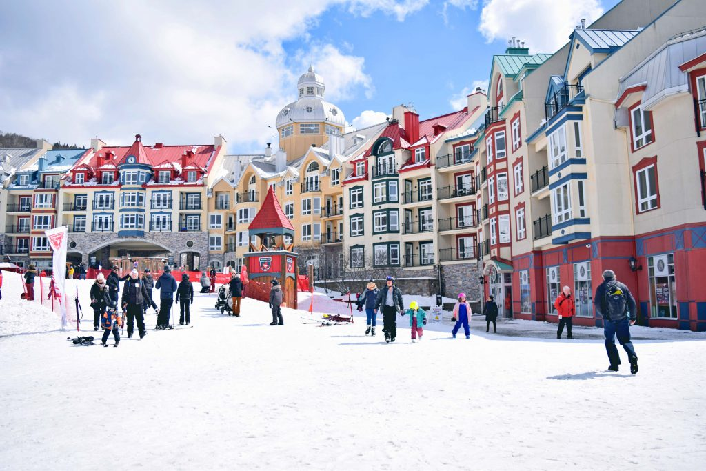 Group of people wandering around ski resort vilalge