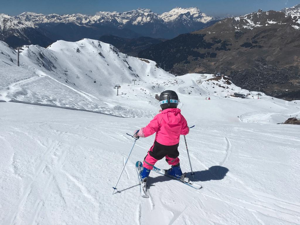 small child in pink ski jacket skiing in Verbier, Switzerland