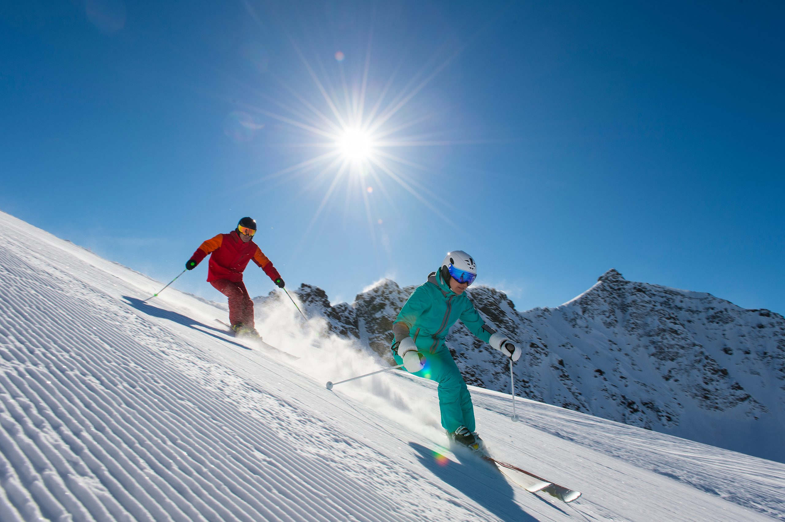two people skiing downhill with sun in the background