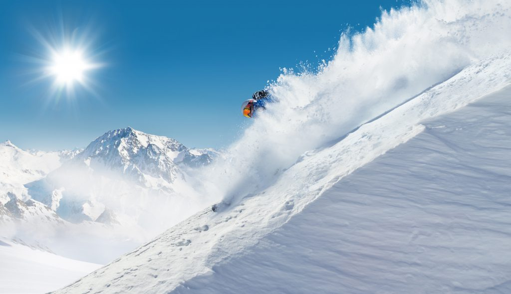 Skier skiing off-piste in high mountains with blue sky